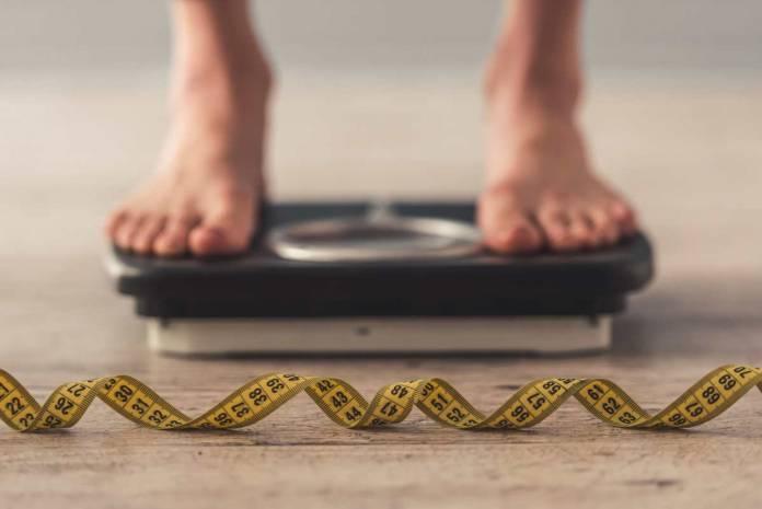 Anoreksja – kobieta stojąca na wadze i leżacy obok centymetr.